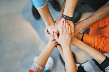 Several people in a circle putting their hands on top of each-other