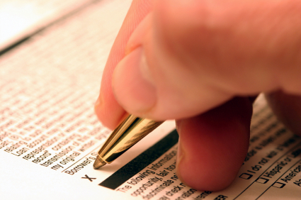 Close up of a hand holding a pen to a document to sign it